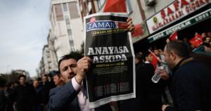 """Un uomo con una copia dell'edizione di sabato di Zaman, con il titolo """"Costituzione sospesa"""", durante una manifestazione fuori dagli uffici del giornale a Istanbul. (AP Photo/Emrah Gurel)"""